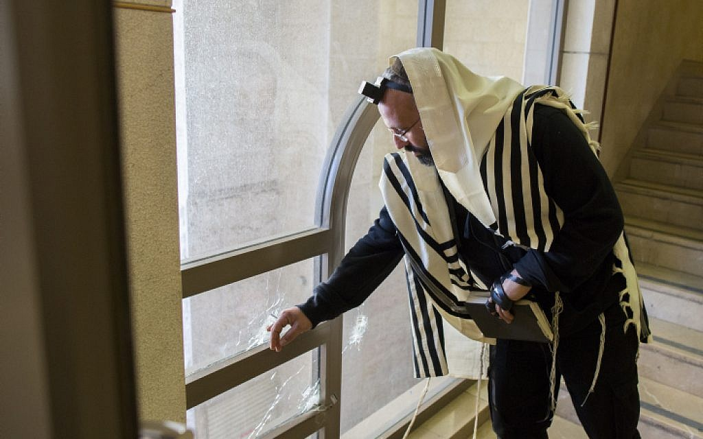 An ultra-Orthodox man examines a bullet hole inside a synagogue where two terrorists from East Jerusalem killed five people the day before. November 19, 2014. (photo credit: Yonatan Sindel/Flash90)