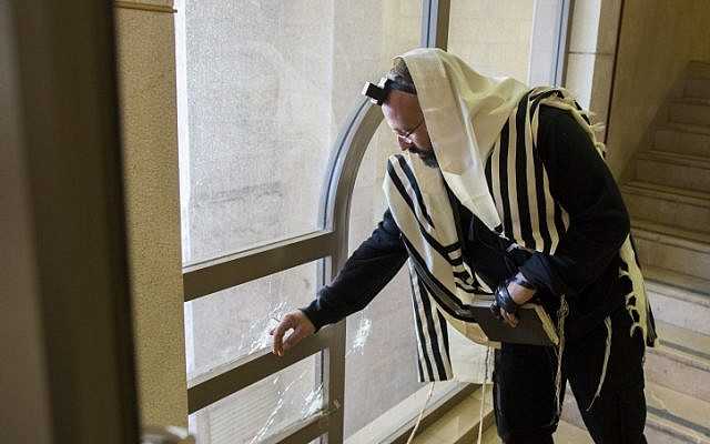 An ultra-Orthodox man examines a bullet hole inside a synagogue where two terrorists from East Jerusalem killed five people on Tuesday. November 19, 2014. (photo credit: Yonatan Sindel/Flash90)
