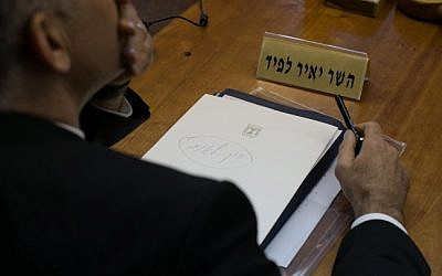 A piece of paper in front of Finance Minister Yair Lapid during the weekly cabinet meeting reads, in handwritten Hebrew, 'National State Law,' Sunday, November 23, 2014. (photo credit: Ohad Zwigenberg/POOL)