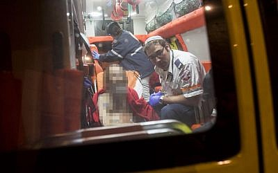 A Jewish man who was stabbed in Jerusalem's Old City is seen (face blurred) sitting in an ambulance on Monday, November 24, 2014 (photo credit: Yoanatn Sindel/Flash90)