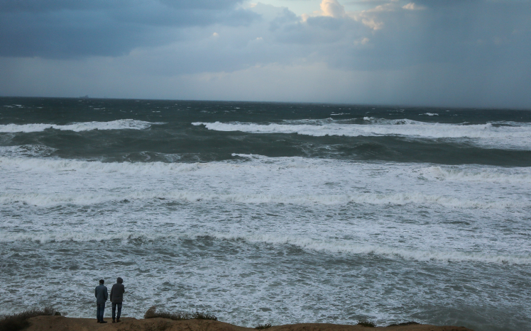 Rain logged capital lashed by winter storm the times of israel israelis look at the sea during a rainstorm in the city of ashkelon on november 26 publicscrutiny Choice Image
