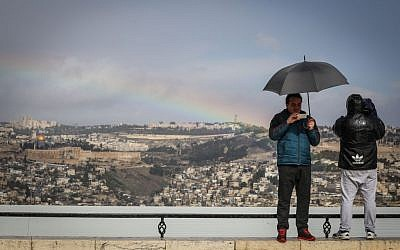 Tourists take a picture of the Old City of Jerusalem at the Armon Hanatziv lookout on a stormy winter day on Novermber 26, 2014. (Photo credit: Hadas Parush/Flash90)