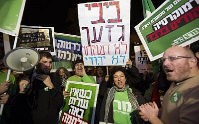 "Left-wing activists hold placards and flags as they protest against the ""Jewish state"" bill near the Prime Minister residence in Jerusalem on November 29, 2014. Some of the placards call Benjamin Netanyahu a racist, and assert that he seeks democracy for Jews only. (Photo credit: Yonatan Sindel/Flash90)"