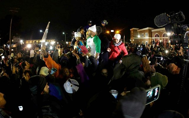 Lesley McSpadden, the mother of Michael Brown, left standing on the top of a car, reacts as she listens to the announcement of the grand jury decision Monday, Nov. 24, 2014, in Ferguson, Mo. (AP Photo/Charlie Riedel)