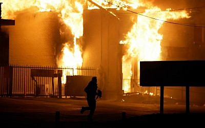 A man runs away from a burning storage facility after the announcement of the grand jury decision Monday, Nov. 24, 2014, in Ferguson, Mo. (AP Photo/David Goldman)