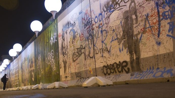 Balloons from the art project 'Lichtgrenze 2014' (lit. 'lightborder 2014') reflected in a puddle next to remains of the Berlin Wall at East Side Gallery in Berlin, Germany, Friday, Nov. 7, 2014. (photo credit: AP/Steffi Loos)