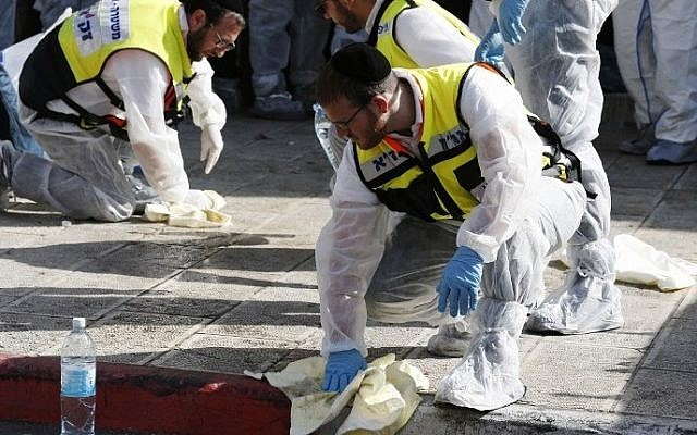 Israeli emergency services personnel gathers blood and other human remains from the sidewalk for proper burial  at the scene of an attack, by two Palestinians, on Israeli worshippers at a synagogue in the ultra-Orthodox Har Nof neighborhood in Jerusalem on November 18, 2014 (photo credit: AFP/Jack Guez)