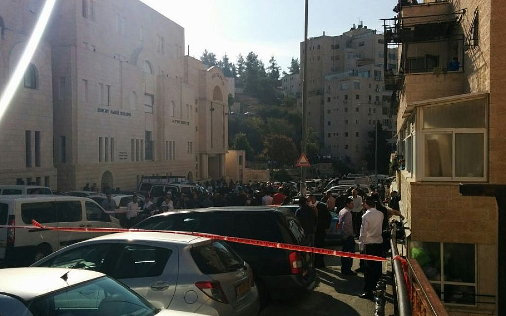 People outside the scene of a terror attack in Jerusalem's Har Nof neighborhood on November 18, 2014. (photo credit: Marissa Newman / Times of Israel)