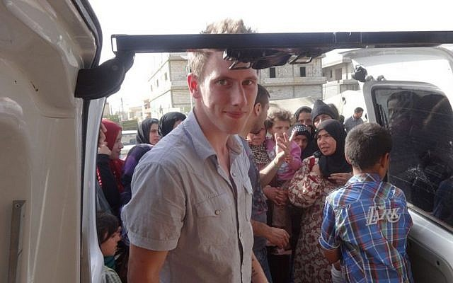 An undated photo shows Peter Kassig delivering supplies for Syrian refugees. (photo credit: AP/Courtesy Kassig Family)