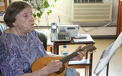 Emily Kessler strums the mandolin in her Upper West Side apartment. (photo credit: Raffi Wineburg/JTA)