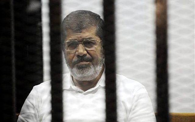 Egypt's former president Mohammed Morsi sits in the defendant's cage during a court hearing in Cairo, Egypt, November 3, 2014. (AP/Mohammed al-Law)