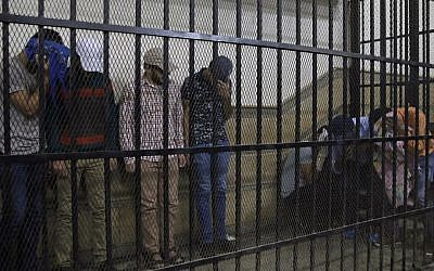 (Illustrative) Eight Egyptian men convicted for 'inciting debauchery' following their appearance in a video of an alleged same-sex wedding party on a Nile boat appear in the defendant's cage in a courtroom in Cairo, Egypt, Saturday, November 1, 2014 (Photo credit: Hassan Ammar/AP)