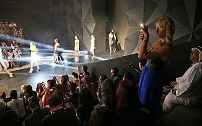 "An Emirati man looks at a woman while she takes snaps of a catwalk during the ""Fashion Forward"" in Dubai, United Arab Emirates. Saturday, April 12, 2014 (photo credit: AP/Kamran Jebreili)"