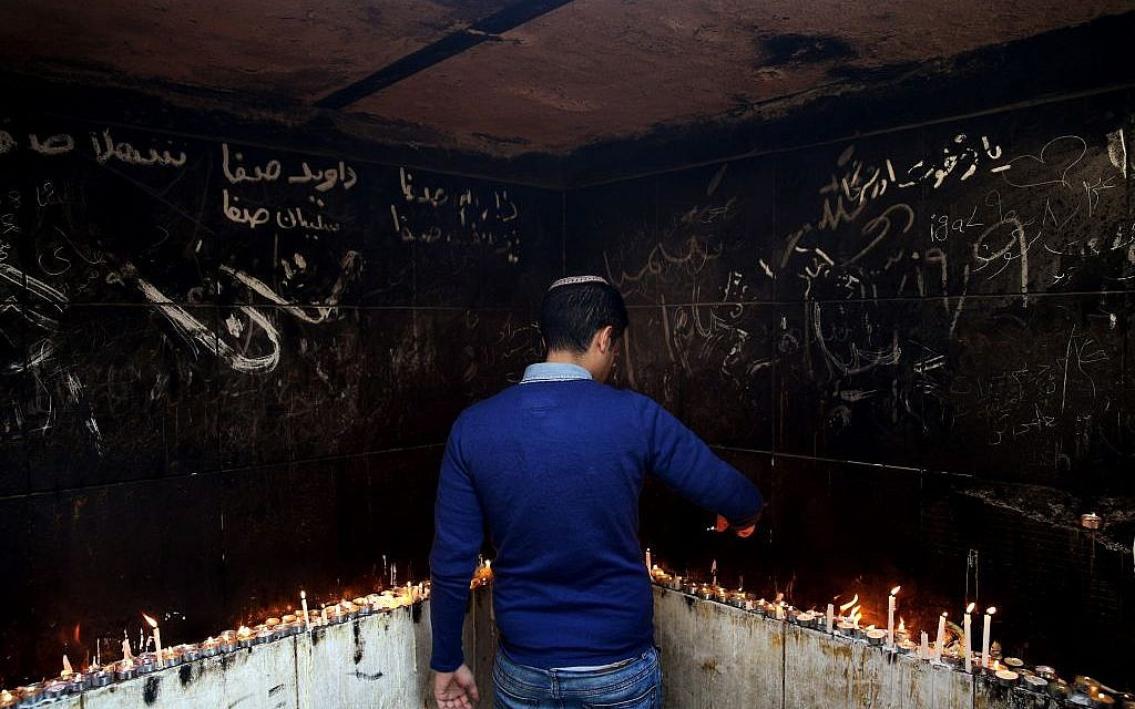In this Thursday, Nov. 20, 2014 photo, an Iranian Jewish man lights candles at the at the tomb of Harav Oursharga, one of the holiest Jewish sites in Iran, in the city of Yazd 420 miles (676 kilometers) south of capital Tehran. (photo credit: AP Photo/Ebrahim Noroozi)