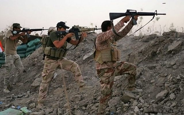 Iraqi Shiite militiamen fire their weapons during clashes with militants from the Islamic State group, in Jurf al-Sakhar, Sept. 28, 2014.  (photo credit: AP, File)