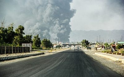 A column of smoke rises from an oil refinery in Beiji, some 250 kilometers (155 miles) north of Baghdad, Iraq, after an attack by Islamic militants,  July 31, 2014. (photo credit: AP, File)