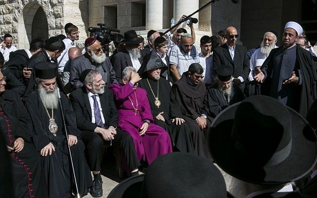 Sheikh Samir Assi, the imam of the Al-Jazaar mosque in the northern Israeli city of Acre, addresses Christian, Muslim and Jewish clerics outside the synagogue where on Tuesday two Palestinian terrorists killed five Israelis, in Jerusalem on Wednesday, Nov. 19, 2014. (Photo credit: AP Photo/Olivier Fitoussi)