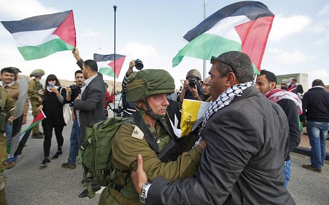 An Israeli soldier and a Palestinian protester face off as protesters try to block a highway between Jerusalem and the Dead Sea near the West Bank town of Jericho Friday, Nov. 28, 2014. (photo credit: AP Photo/Nasser Shiyoukhi)