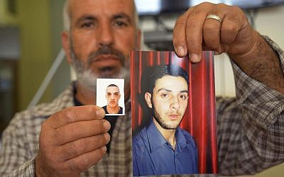 A relative displays photos of cousins Ghassan, right, and Uday Abu Jamal at the family home in the East Jerusalem neighborhood of Jabel Mukaber, Tuesday Nov. 18, 2014 (photo credit: AP/Mahmoud Illean)