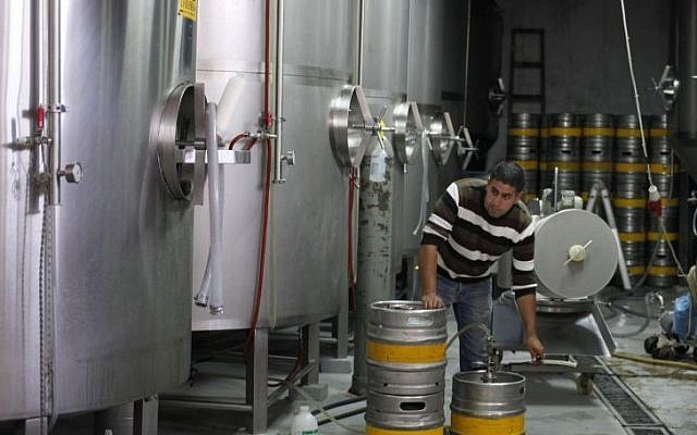 A man works at the Palestinian Taybeh brewery in Taybeh, West Bank, October 28, 2014 (Photo credit: Nasser Shiyoukhi/AP)