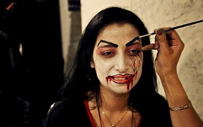 In this Thursday, Oct. 30, 2014, photo, a woman gets her face painted before entering a Halloween party in an upscale Damascus hotel. Amid a conflict grinding well into its fourth year, Syrians have sought to deny war its miserable monotony by taking pleasure in mindless entertainment, ranging from lounging in cafes, to dancing to thumping discos. (photo credit: AP Photo/Diaa Hadid)