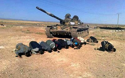 In this April 30, 2014, file image provided by the Syrian Revolution Against Bashar Assad, which has been authenticated based on its contents and other AP reporting, Syrian rebels pray in front of their tank at al Mutayia village in the southern province of Daraa, Syria. (photo credit: AP/the Syrian Revolution Against Bashar Assad)