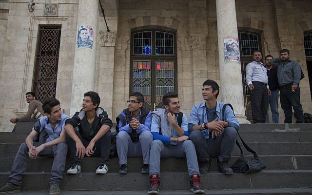In this photo taken Sunday, Oct. 26, 2014, young men sit on the stairs of the Ottoman-era Hijaz train station in the Syrian capital, Damascus. (photo credit: AP/Diaa Hadid)