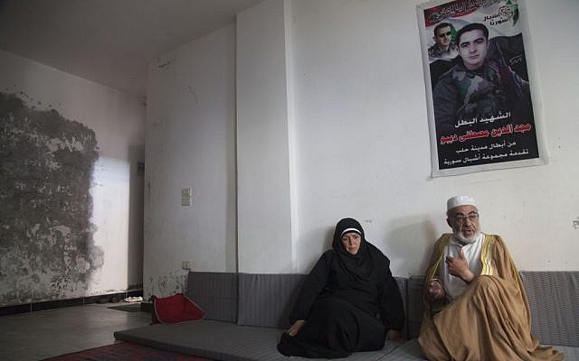In this Tuesday, Oct. 28, 2014 photo, Mustafa Sobhi, 53, and his wife Faten Shaar, 52, sit under a portrait of their son Majed, who was killed while serving in the Syrian army, at a shelter in Tartous, Syria. The family was forced to flee the northern Syrian city of Aleppo to the coastal city of Tartous.  (photo credit: AP/Diaa Hadid)