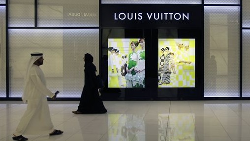 """Emirati nationals pass by a """"Louis Vuitton"""" fashion store at a shopping mall in Dubai, United Arab Emirates. Although the UAE is one of the wealthiest countries in the region, the gap between its richest families and everyone else is vast. Thursday, April 25, 2013 (Photo Credit: AP /Kamran Jebreili)"""