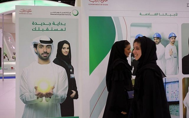 Emirati women pass by posters at a government stand during the Careers UAE opening exhibition exclusively for UAE Nationals in Dubai, United Arab Emirates. UAE's late leader Sheik Zayed bin Sultan Al Nahyan patronized tribes and villages under his leadership by establishing an expansive welfare program that younger generations of Emiratis have come to expect. This gravy train has created a vast middle class of Emiratis who almost entirely rely on the government for jobs and benefits to maintain their standard of living. Tuesday, April 22, 2014 (photo credit: AP/Kamran Jebreili)