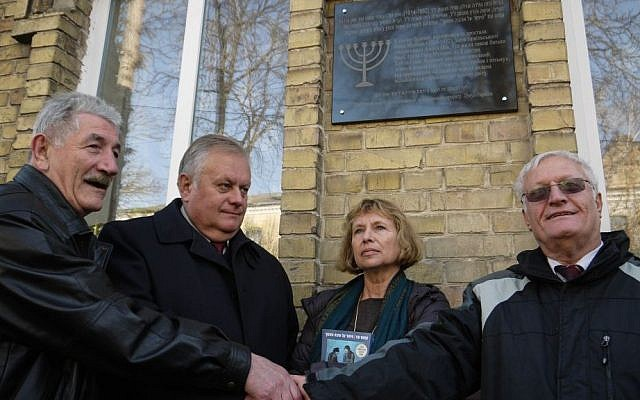 From left: Rivne Jewish community leader Gennady Frayerman, Rivne Mayor Volodymyr Khomko, Haifa University Professor Fania Oz-Salzberger and Limmud FSU co-founder Chaim Chesler shake hands after unveiling a plaque outside the house in which Oz-Salzberger's grandmother Fania Mussman, the mother of celebrated Israeli author Amos Oz, grew up, in Rivne, Ukraine, Monday, November 10, 2014( photo credit: Yifa Yaakov/The Times of Israel)