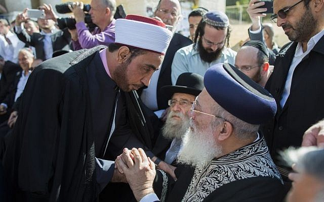 Jerusalem's chief rabbi Shlomo Amar (right, seated) shakes hands with an imam as leaders from the Christian and Muslim communities show their support outside Kehilat Yaakov Synagogue in the Jerusalem neighborhood of Har Nof, one day after two Palestinian terrorists entered the synagogue with a pistol and meat cleavers and killed four worshipers, November 19, 2014. (photo credit: Yonatan Sindel/Flash90)