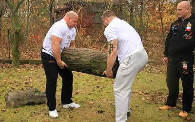 Members of the Polish Strongman Federation, headed by former world champion Tomasz Kowal (left) remove a Jewish gravestone from an urban farm plot in Warsaw. (courtesy From the Depths)