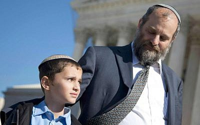 Ari Zivotofsky (right), stands with his nine-year-old son, Menachem, outside the Supreme Court in Washington, DC,  November 7, 2011. (photo credit: AP/Evan Vucci, File)