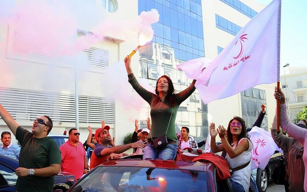 Supporters of Tunisian party Nida Tunis (Tunisia Calls) celebrate their victory in parliamentary elections in Tunis, October 28, 2014. (photo credit: AP/Hassene Dridi)