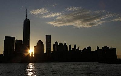 The sun rises next to One World Trade Center, Monday, Nov. 3, 2014 in this view from Jersey City, N.J. Thirteen years after the 9/11 terrorist attack, the resurrected World Trade Center is again opening for business, marking an emotional milestone for both New Yorkers and the United States as a whole. (photo credit: AP Photo/Mark Lennihan)