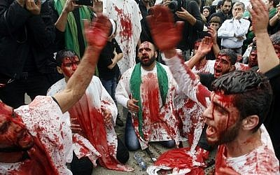 Lebanese Shiite Muslims take part in a self-flagellation procession during the Ashura commemorations that mark the killing of Imam Hussein -one of Shiite Islam's most revered figures- on November 4, 2014 in the southern Lebanese city of Nabatiyeh. (photo credit: AFP PHOTO / MAHMOUD ZAYYAT)