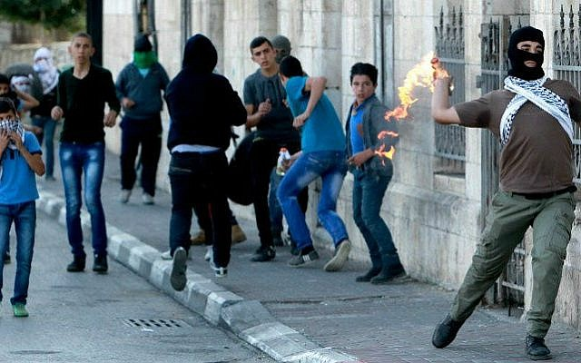 A masked Palestinian throws a firebomb at Israeli forces at the main entrance of the West Bank town of Bethlehem on November 11, 2014 (photo credit: AFP/ Musa Al Shaer)