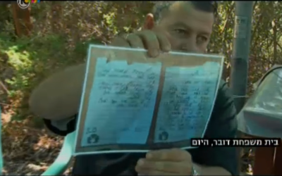 Boris Dauber, the father of fallen IDF soldier First Sgt. Shahar Dauber, with a laminated copy of his son's farewell letter (screen capture: Channel 10 news)