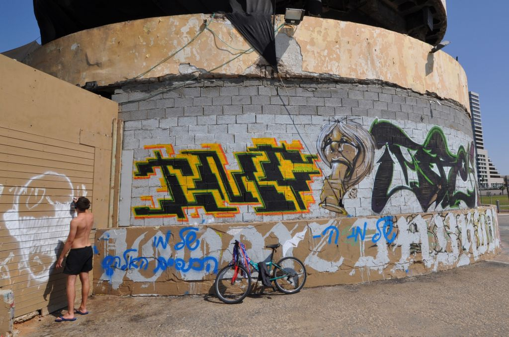 A man sprays graffiti on the sea-facing side of the abandoned Dolphinarium building in Tel Aviv in 2013. (Photo credit: Hannah Morrow/Flash90)