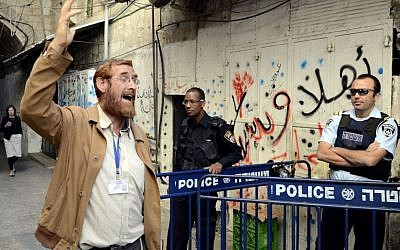 Yehudah Glick walks by Israeli border police after leaving the Temple Mount compound in Jerusalem's Old City, October 10, 2013. (Sliman Khader/FLASH90)
