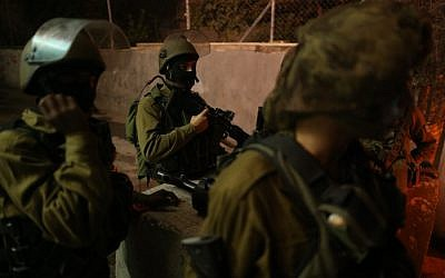 Israeli soldiers seen at the entrance to the Palestinian village of al-Aroub in the West Bank, where three Israeli soldiers were injured when a Palestinian driver rammed his car into them, close to the Gush Etzion Junction, November 5, 2014. (photo credit: Nati Shohat/Flash90)