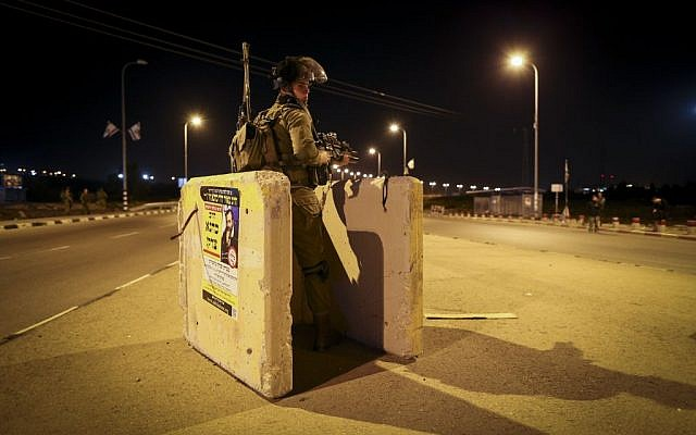 An Israeli soldier stands guard near the site where a young Jewish woman was killed by a Palestinian terrorist, and two people were injured in a stabbing attack at a bus stop at the entrance to the West Bank settlement of Alon Shvut, on November 10, 2014. (photo credit: Nati Shohat/Flash90)