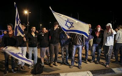 Right-wing Jewish activists wave the Israeli flag as they attend a protest near the site where a young Jewish woman was killed by a Palestinian terrorist, and two people were injured in a stabbing attack at a bus stop at the entrance to the West Bank settlement of Alon Shvut, on November 10, 2014. This is the second terrorist attack of its kind in a day. Earlier today a young Israeli soldier was stabbed by a Palestinian man at a train station in Tel Aviv. (Photo credit: Nati Shohat/Flash90)