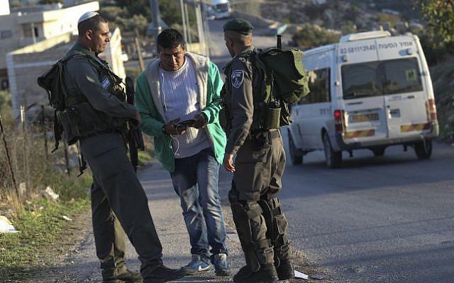 Israeli border police check the identification papers of Arab-Israelis outside the East Jerusalem neighborhood of Jabel Mukaber, November 19, 2014.  (photo credit: Nati Shohat/FLASH90)