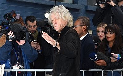 Singer Bob Geldof waves to fans as he arrives at a music studio to record his segment of the new Band Aid 30 charity single in London, Saturday, Nov. 15 2014. (Photo credit: Jonathan Short/Invision/AP)