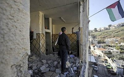 Palestinians hang their national flag inside the demolished apartment of Abdel Rahman al-Shaludi in East Jerusalem, November 19, 2014. (photo credit: AP Photo/Mahmoud Illean, File)