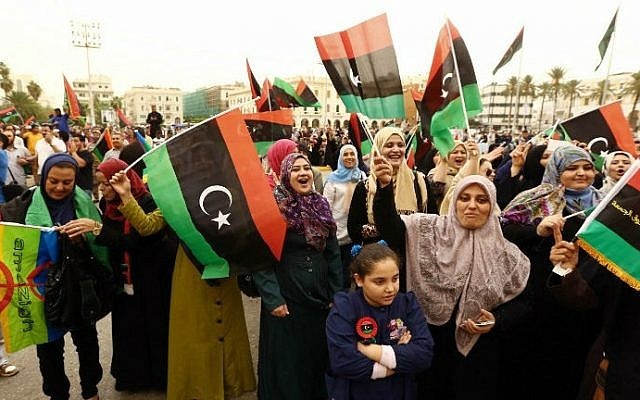 Libyans wave the national flag in a square in Tripoli, November 6, 2014 (photo credit: Mahmud Turkia/ AFP)