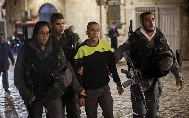 Police escort an Arab youth suspected of stabbing a Jewish man in Jerusalem's Old City on November 24, 2014 (photo credit: Yonatan Sindel/Flash90)