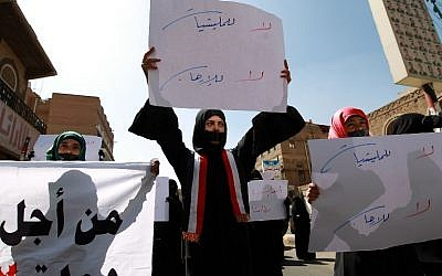 """Yemeni activists carry placards during a rally in Sanaa, on November 8, 2014, against the control by Shiite Huthi fighters and condemning the assassination Mohammad bin Abd al-Malik al-Mutawakkil. Arabic writing on placard (C) reads """"No to militias, no to terrorism."""" (Photo credit: AFP/ Mohammed Huwais)"""
